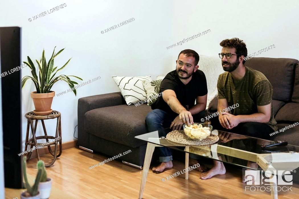 Stock Photo: Male friends watching sports on TV while sitting over sofa in living room.