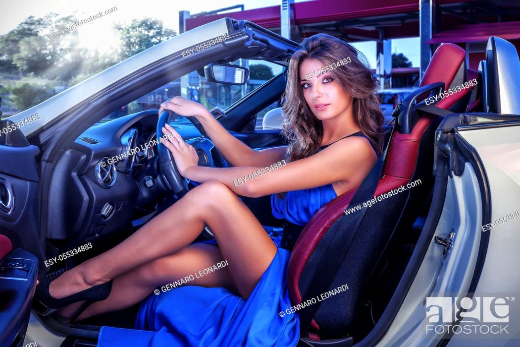 Stock Photo: Girl in long blue dress driving convertible sports car. Woman in luxury car.