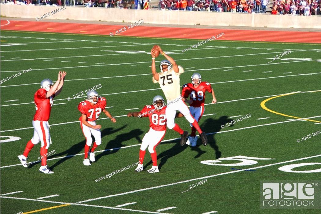Stock Photo: Football player catching football.