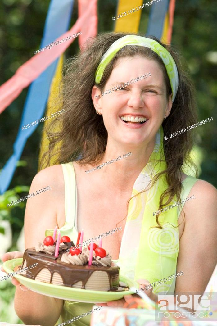 Stock Photo: Mature woman holding a birthday cake and smiling.
