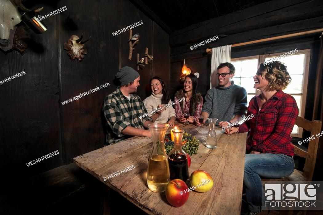 Stock Photo: Group of young people drinking in mountain hut.