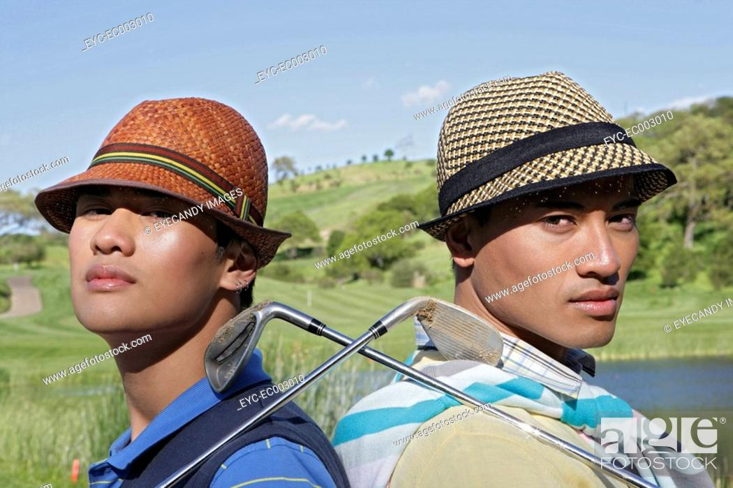 Stock Photo: Portrait of two young men with their golf clubs.