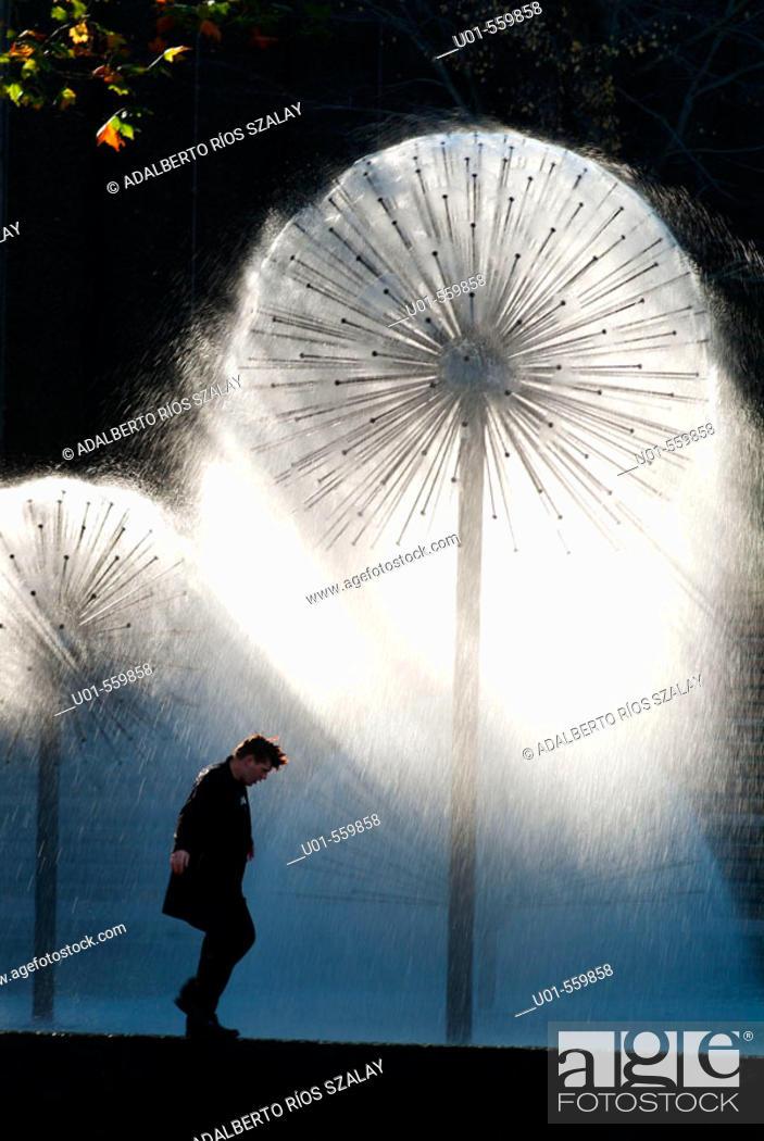 Stock Photo: Young Man Walking Next to Fountain.