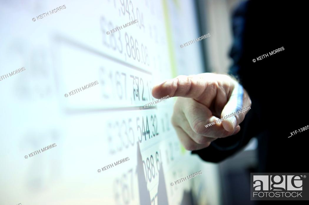 Stock Photo: A man presenting a spreadsheet of figures on a digital whiteboard.
