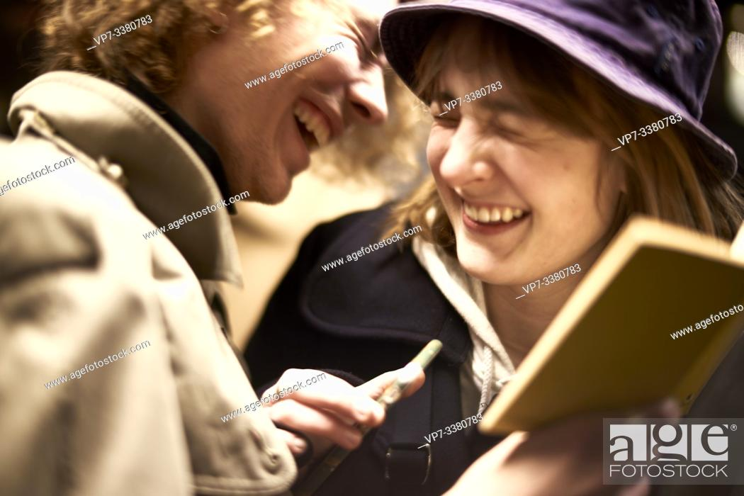 Stock Photo: Couple looking at book, laughing. Nightlife, in Berlin, Germany.