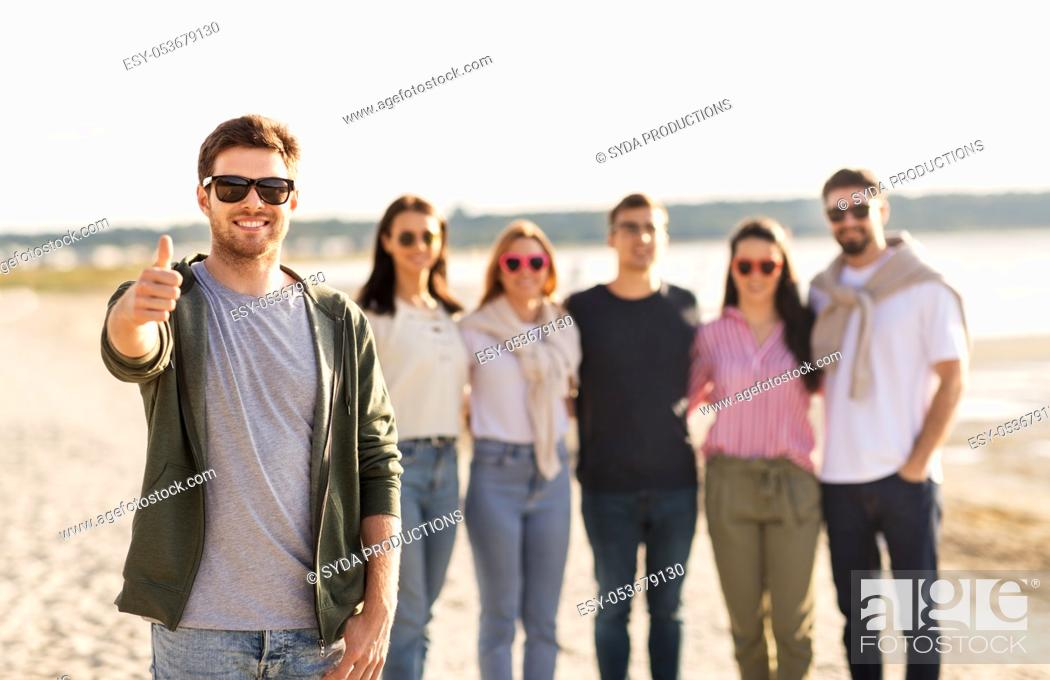 Imagen: happy man with friends on beach showing thumbs up.