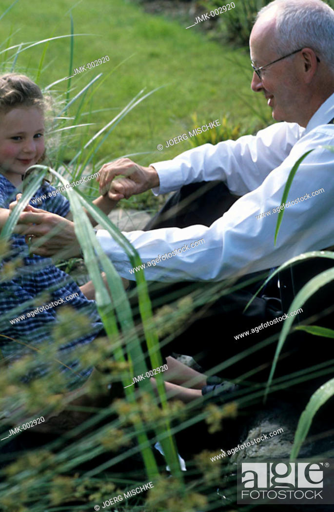 Stock Photo: A senior, businessman, father, grandfather, 45-50 50-55 55-60 years old, and a little girl, 1-5 5-10 years old, sitting at a pond, at the water.