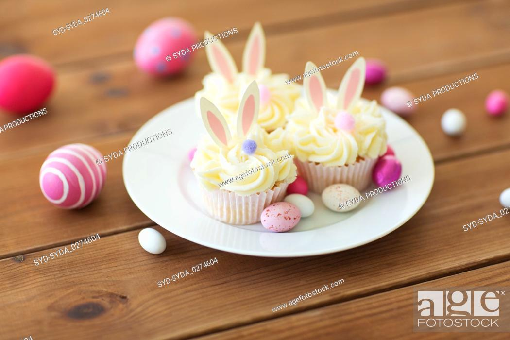Stock Photo: cupcakes with easter eggs and candies on table.