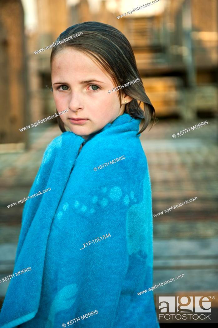 Stock Photo: Ten year old girl wrapped in a blue towel after swimming in the sea, wet hair, looking at the camera.