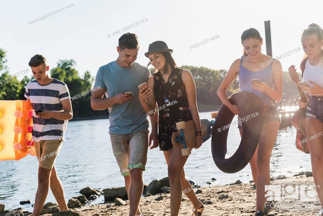 Imagen: Group of friends with cell phones walking at the riverside.