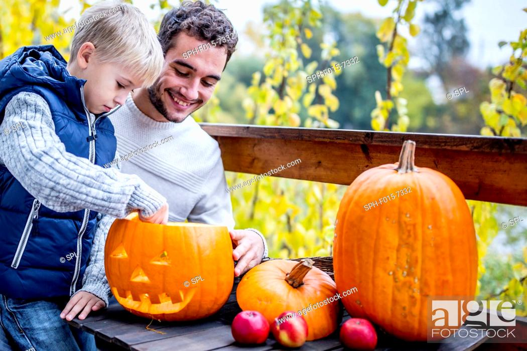 Stock Photo: MODEL RELEASED. Father and son making Halloween pumpkin.