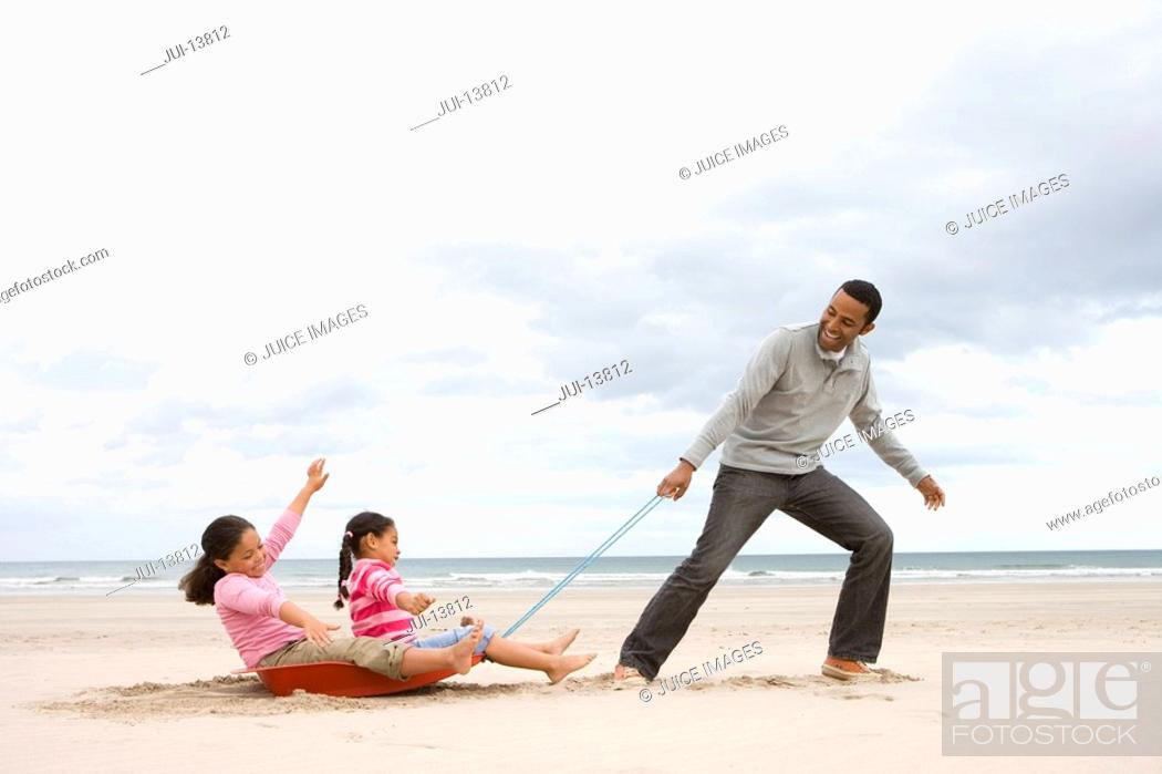 Stock Photo: Father pulling daughters 5-9 on sledge on beach, side view.