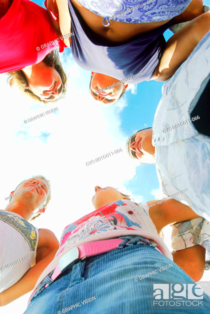 Stock Photo: Low angle view of a group of young people standing in a circle.