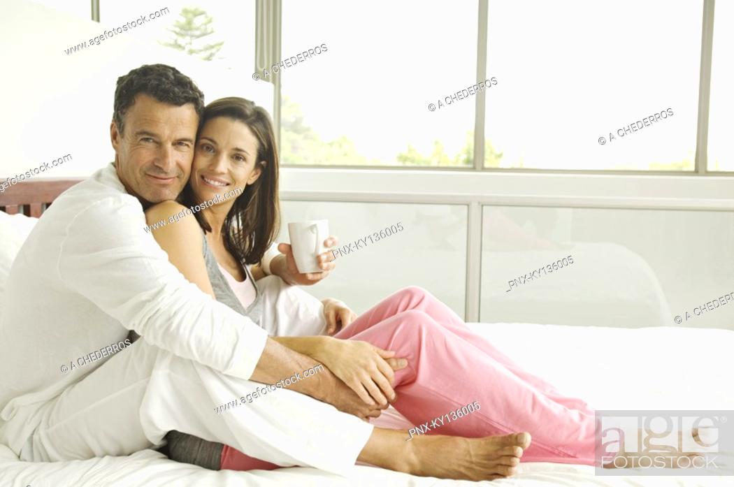 Stock Photo: Couple sitting on bed, looking at the camera, indoors.