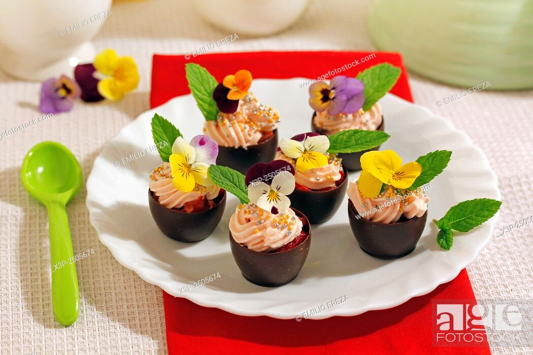 Stock Photo: Chocolate cups with cream and flowers.