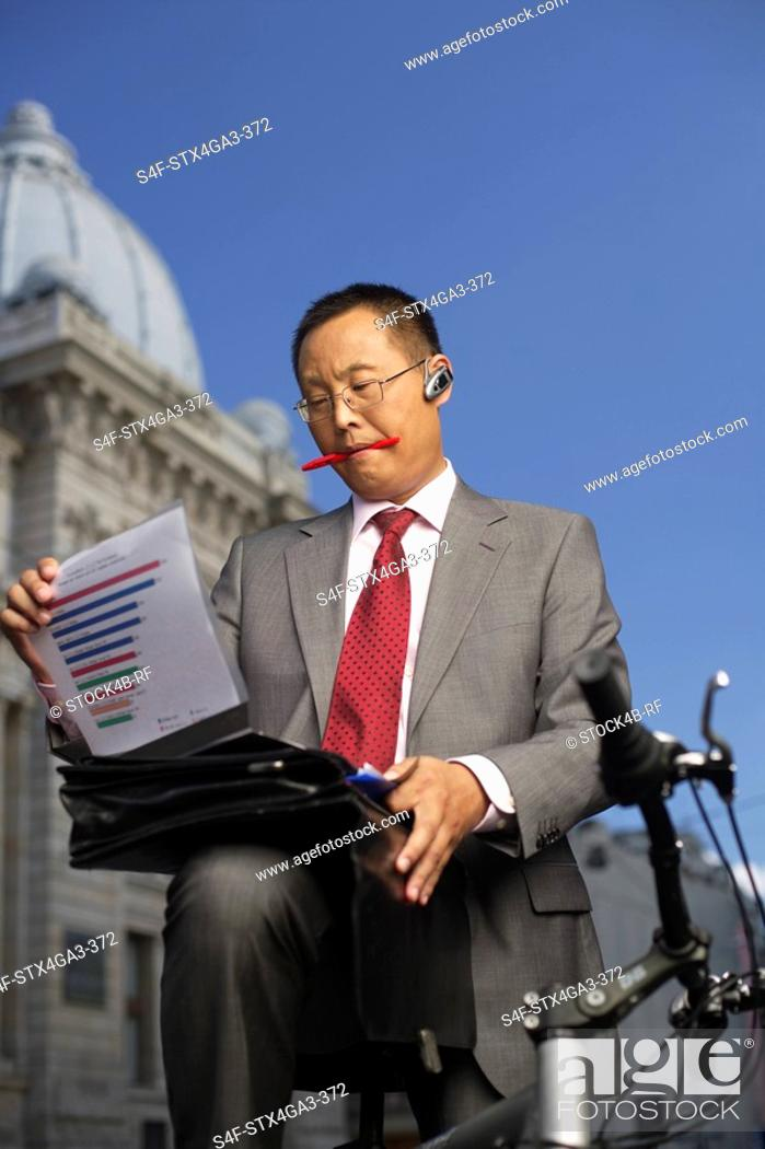 Stock Photo: Businessman watching files outdoors.