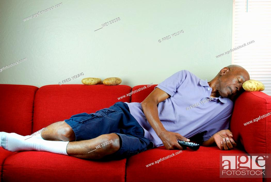 Stock Photo: A senior citizen sleeping on a couch with a remote control in hand and potatoes on the couch.