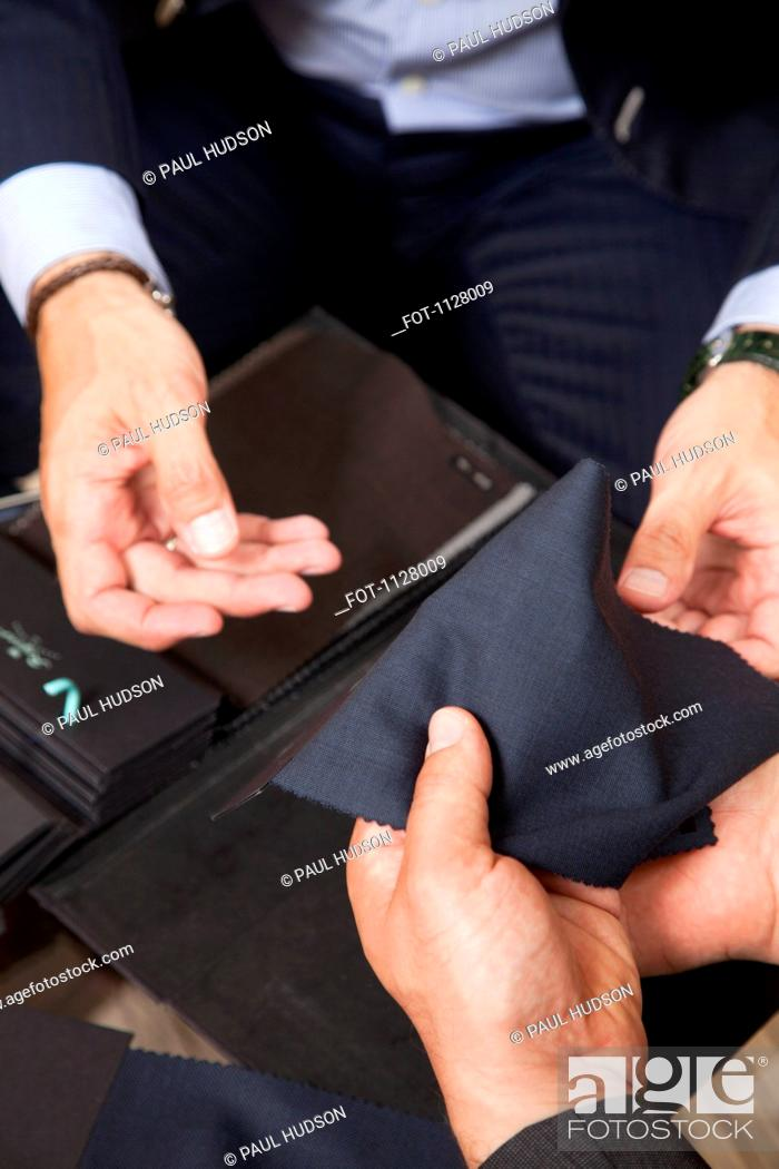 Stock Photo: Detail of two men holding fabric samples.