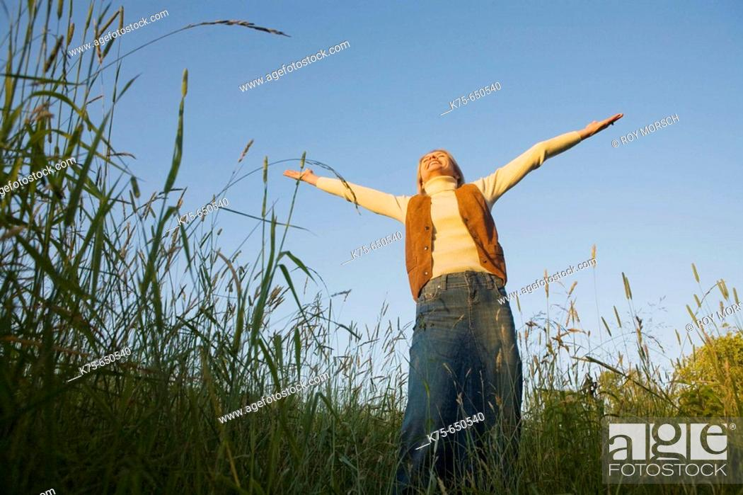 Stock Photo: woman standing with arms outstretched.