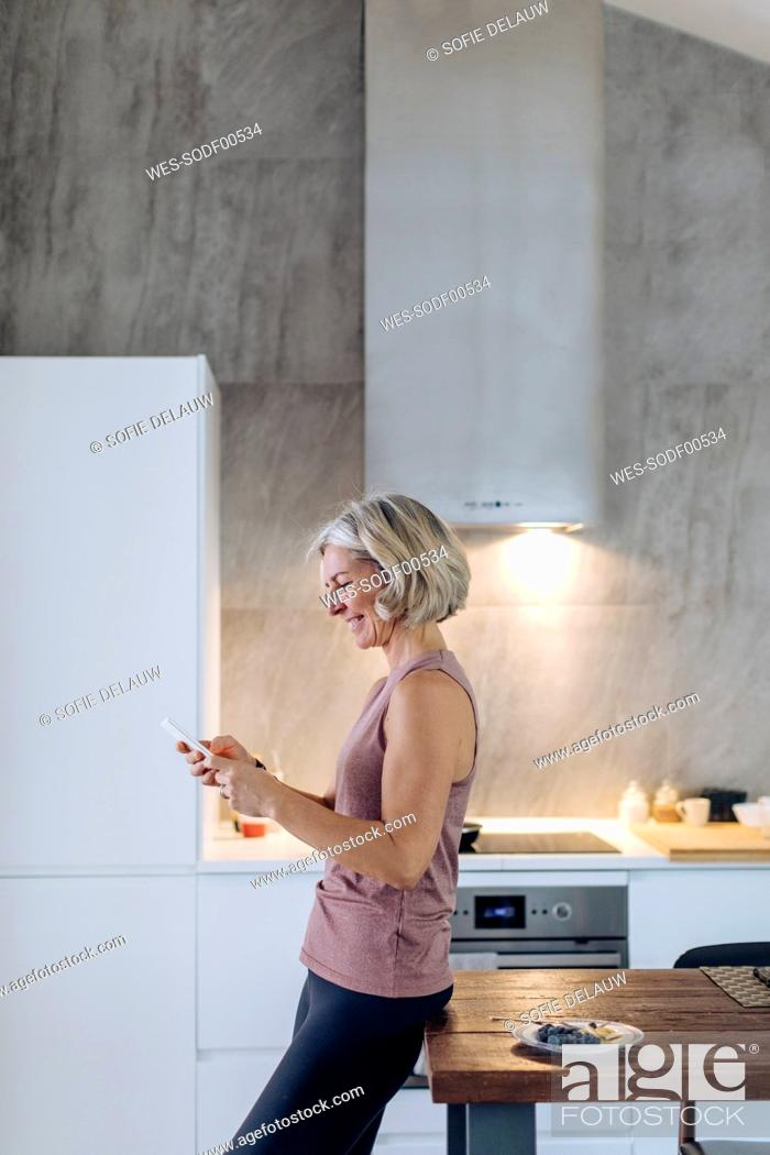 Stock Photo: Mature woman using cell phone in kitchen at home.