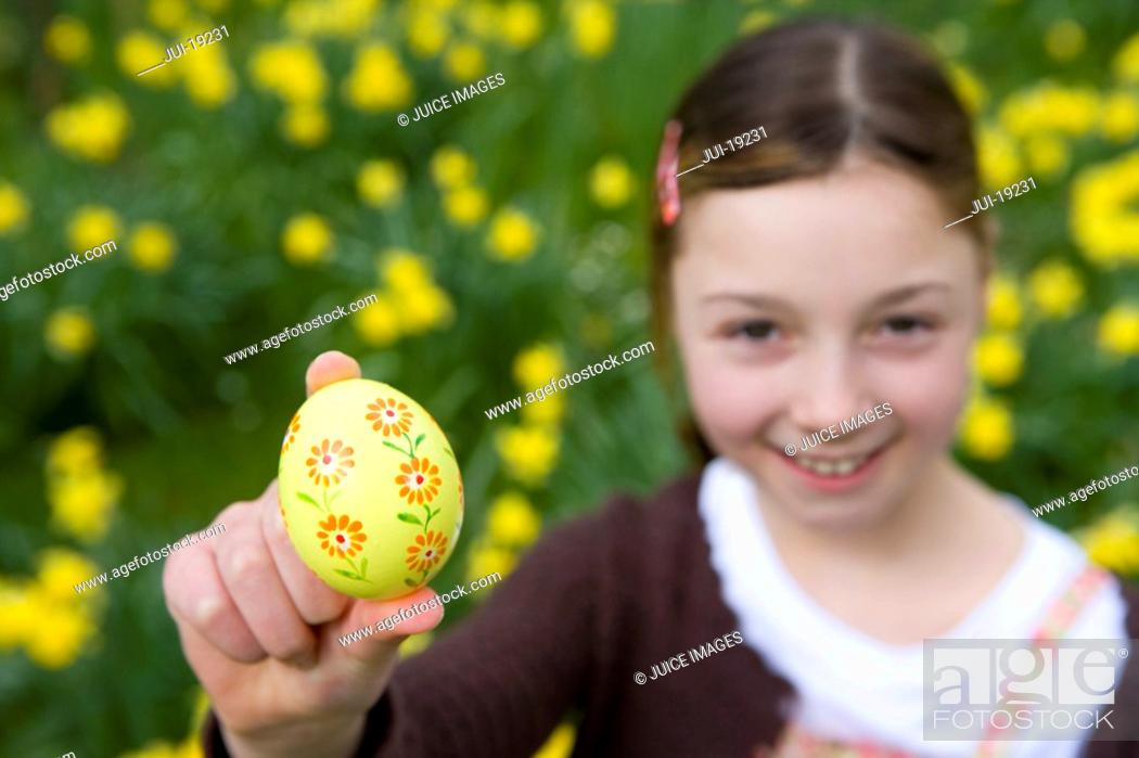 Stock Photo: Young girl holding decorated Easter egg.