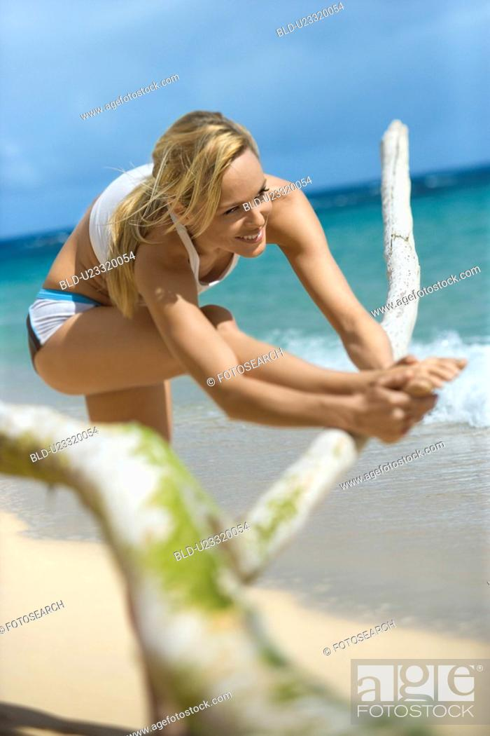 Stock Photo: Woman stretching on beach.