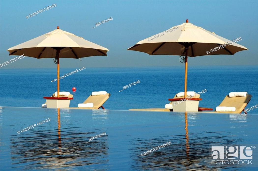 Stock Photo: View across the swimming pool of sun loungers, sunshades and the ocean, Chedi Hotel, Muscat, Sultanate of Oman, Middle East.