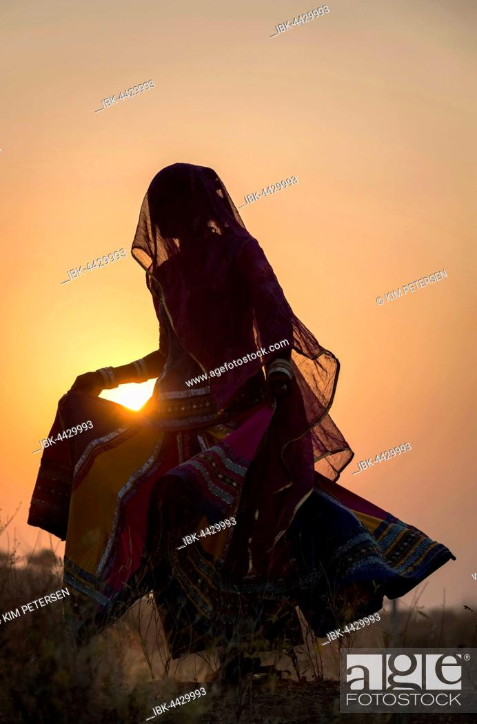 Stock Photo: Woman dancing in front of the sun, Pushkar, Rajasthan, India.