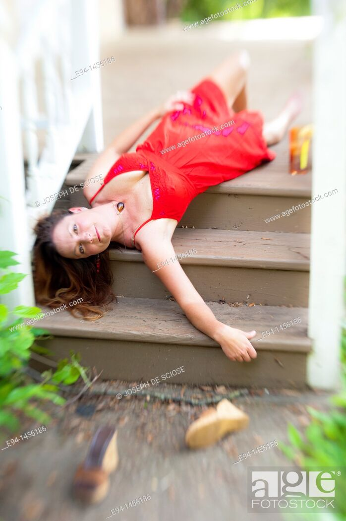 Stock Photo: A 36 year old brunette woman in a red summer dress lying on her back on porch steps looking directly at camera.