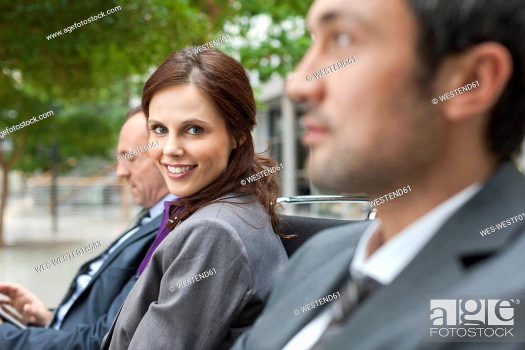 Stock Photo: Germany, Leipzig, Business people sitting on bench, smiling.