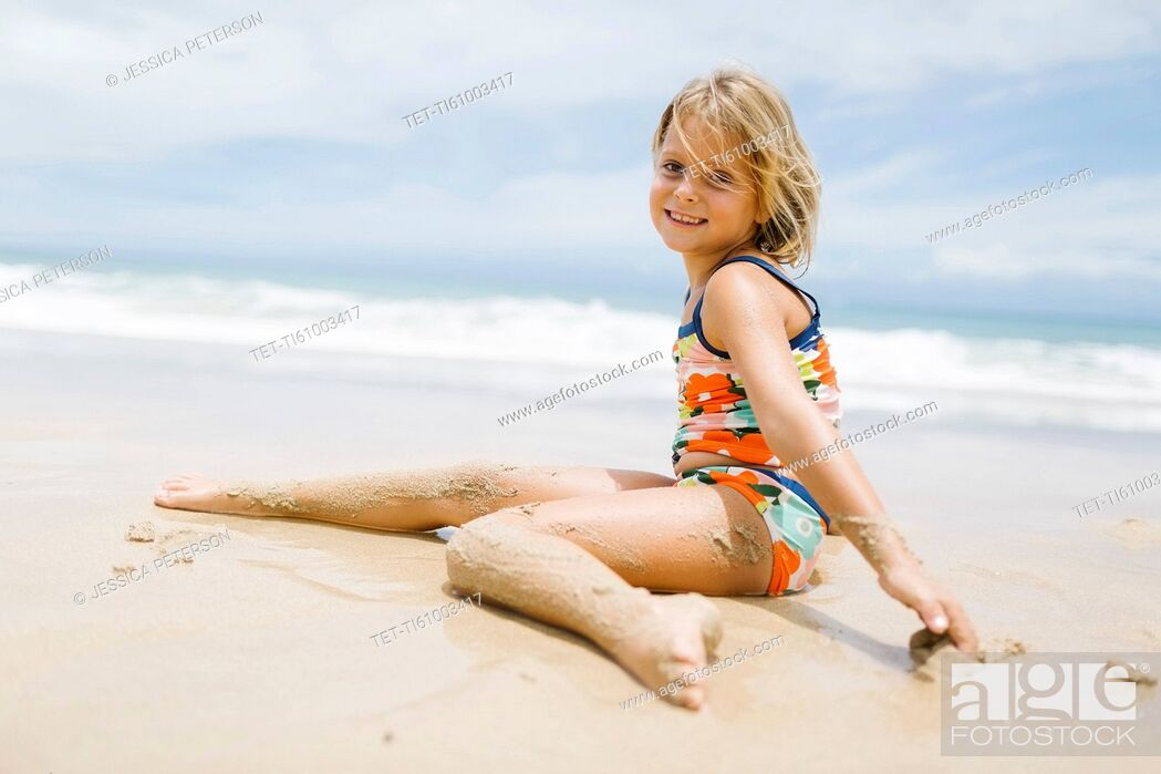 Stock Photo: Girl (6-7) sitting on beach.