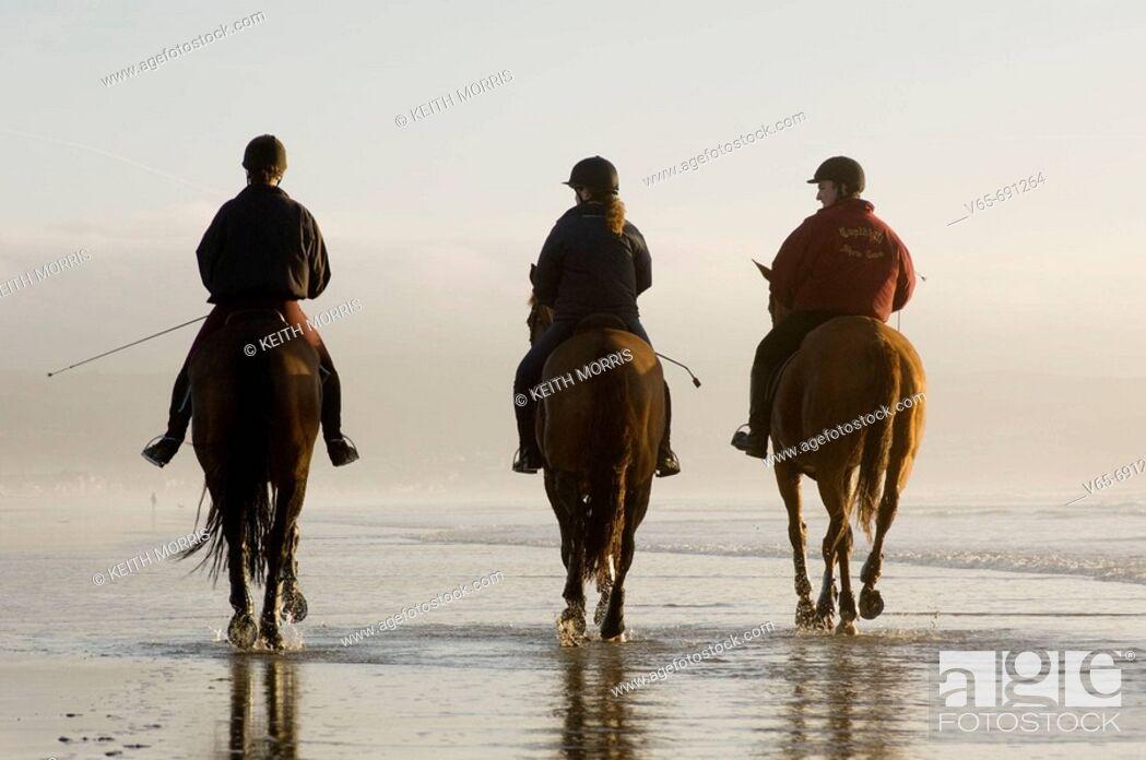 Stock Photo: Three people riding horses on Ynyslas beach, Borth, Ceredigion, West Wales, January afternoon.