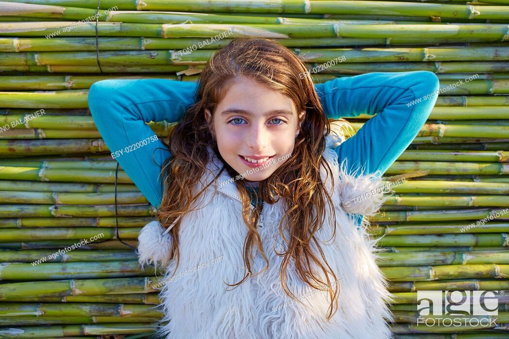 Stock Photo: Kid girl relaxed in green canes background in autumn winter.