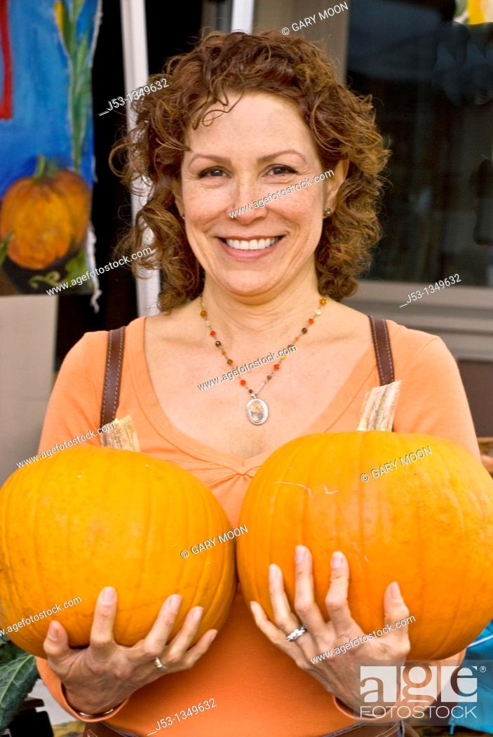 Stock Photo: Woman holding two pumpkins at farmers' market, Nevada City, California.