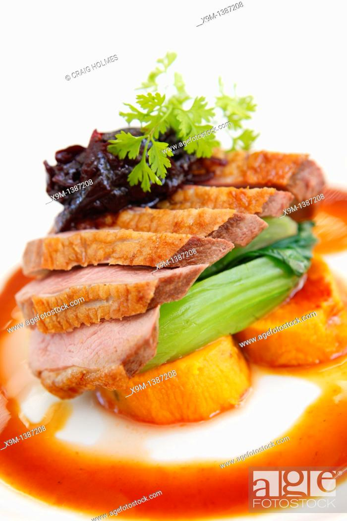 Stock Photo: Roast duck breast on a bed of vegetables with cranberry sauce and gravy.