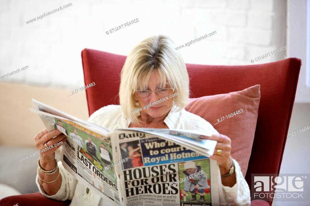 Stock Photo: Senior woman reading newspaper.