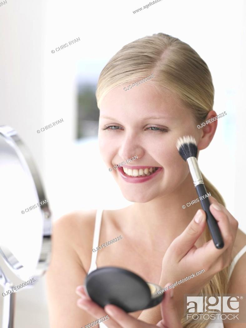 Stock Photo: Woman smiling and applying makeup with cosmetic brush and compact mirror.