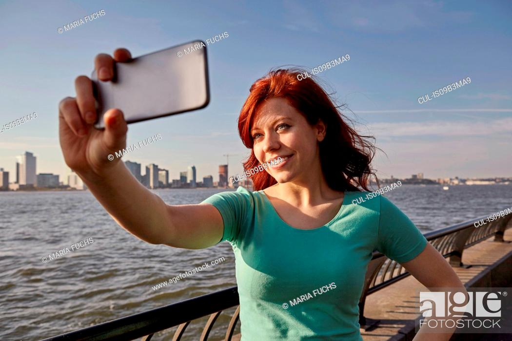 Stock Photo: Young female tourist with long red hair taking selfie on waterfront, Manhattan, New York, USA.