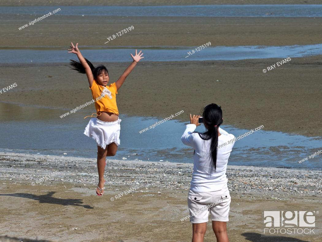Stock Photo: A mother taking a photograph of her leaping daughter on a beach  Asia.