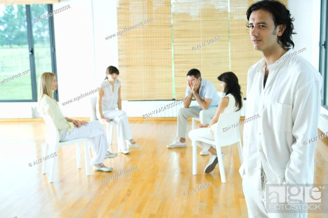 Stock Photo: Group sitting in circle while man stands in foreground.