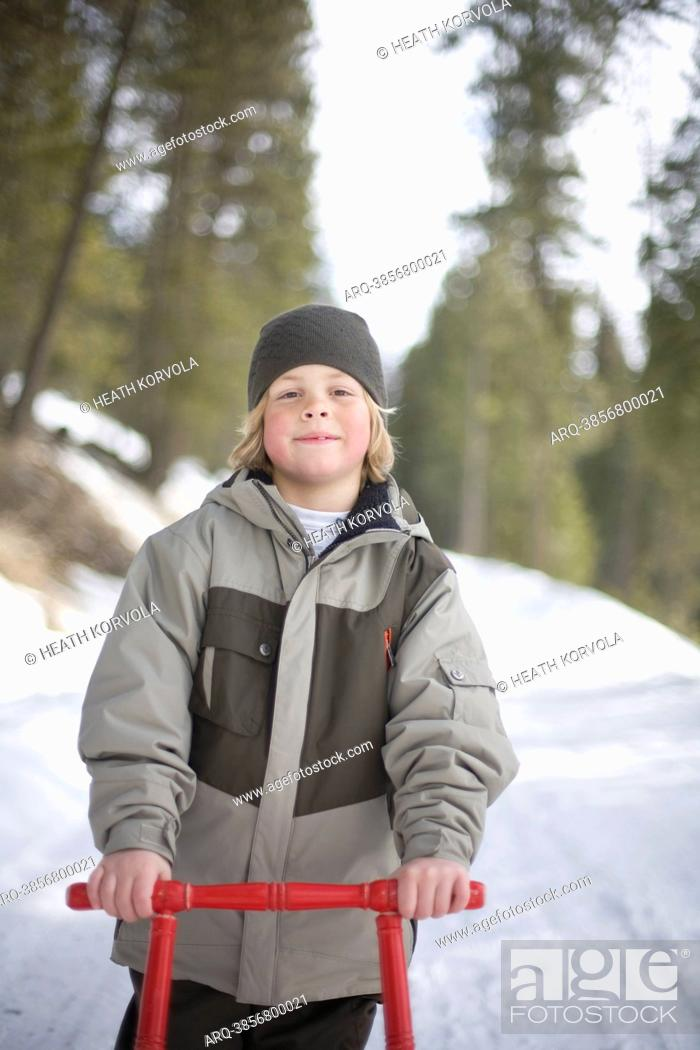 Stock Photo: A portrait of a young boy and his sled outside on a snowy road.