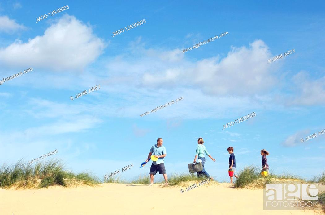 Stock Photo: Vacationing Family walking along beach.