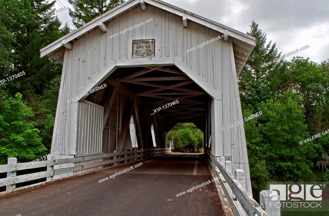 Stock Photo: This vintage white covered bridge is a historic landmark in Linn County, Oregon  This is Hoffman bridge, built in the 1930's circa, over Crabtree Creek.