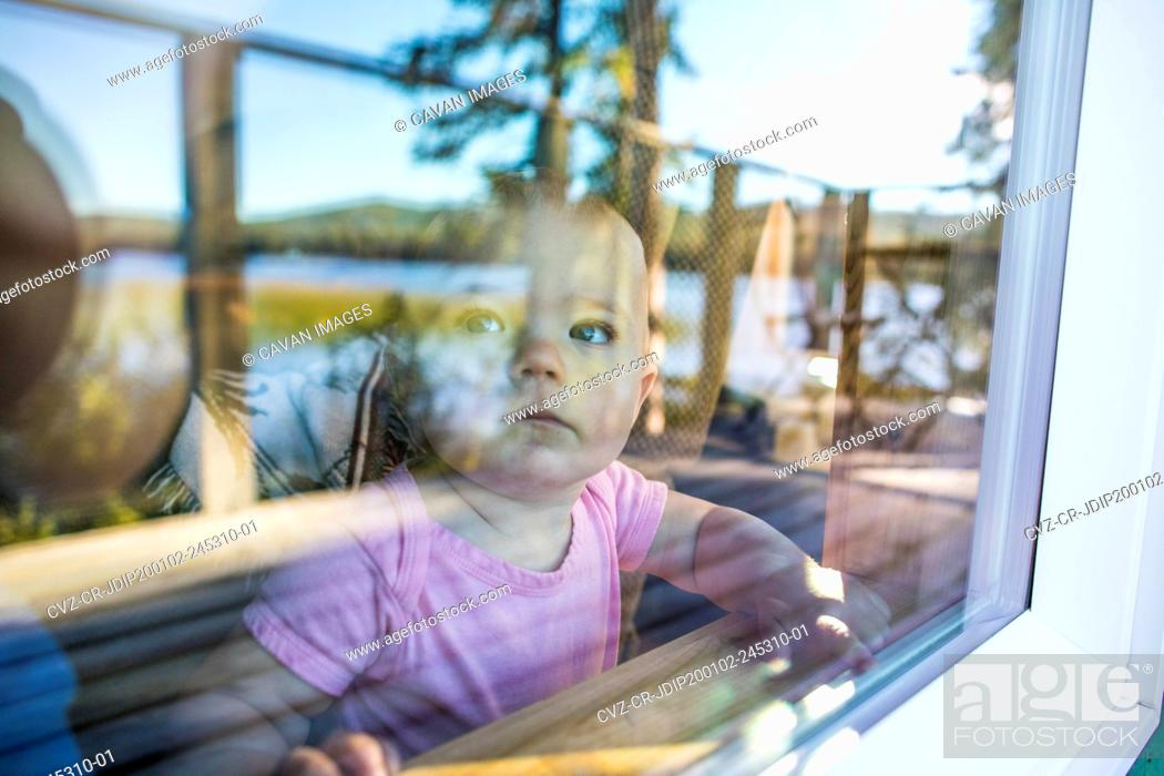 Stock Photo: Young girl looking out through window.