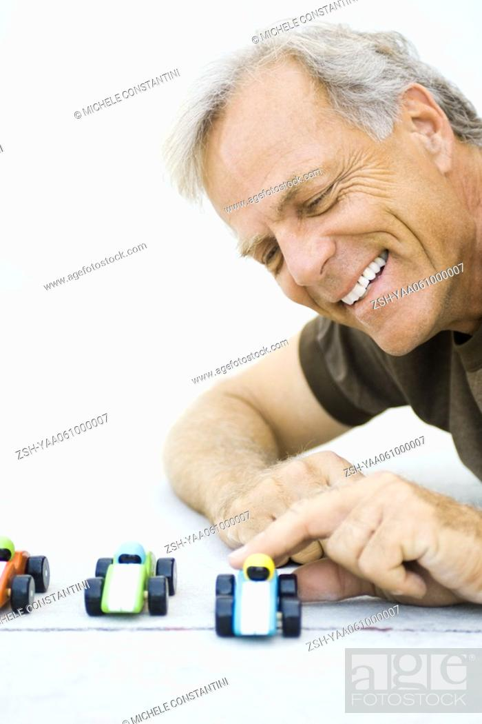 Stock Photo: Mature man playing with toy cars, smiling, close-up.