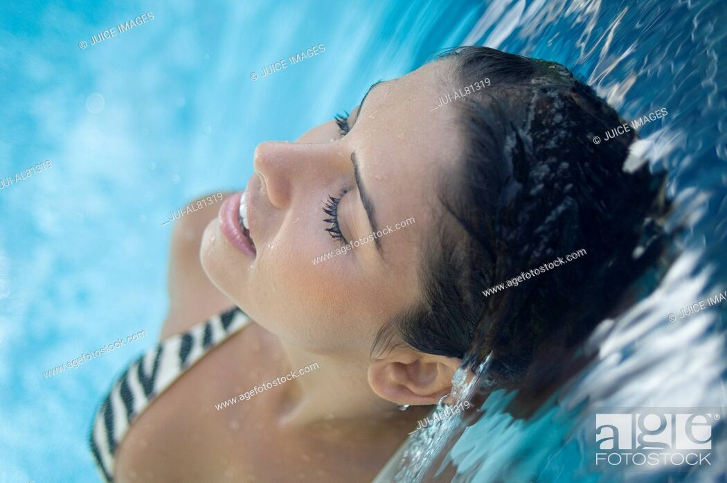 Stock Photo: High angle view of woman standing under waterfall.