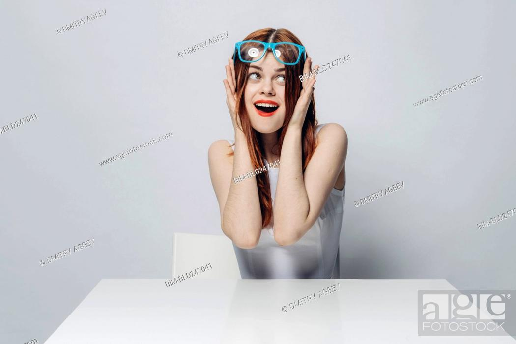 Stock Photo: Happy Caucasian woman sitting at table lifting blue eyeglasses.