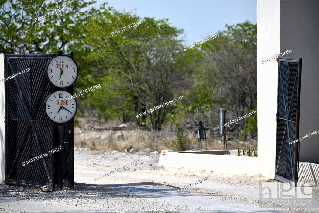 Stock Photo: When entering and leaving a camp site in Etosha National Park, two attached clocks indicate when the goal opens at dawn and when it closes due to the oncoming.