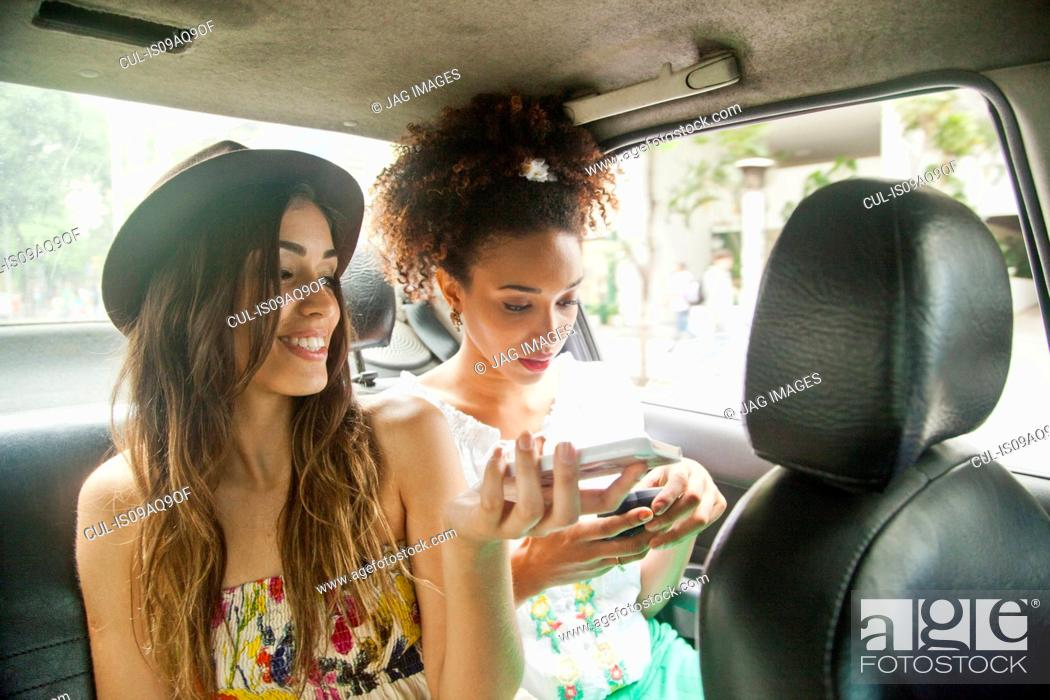 Stock Photo: Two young women in back of car, using smartphones.