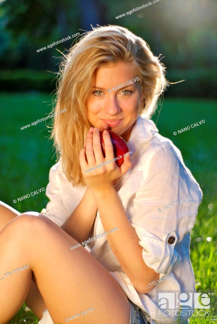 Stock Photo: Attractive young blonde woman in nature, holding a fresh apple.